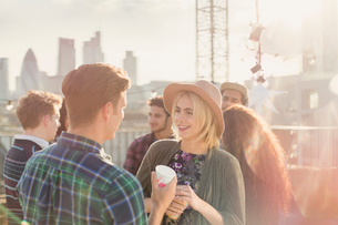 Young man and woman drinking and talking at rooftop partyの写真素材 [FYI02171001]