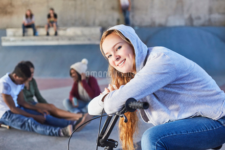 Portrait smiling teenage girl leaning on BMX bicycle at skate parkの写真素材 [FYI02171048]