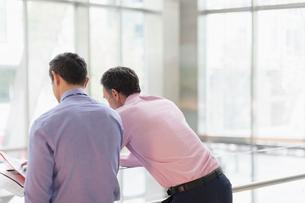Corporate businessmen reviewing paperwork at railing in officeの写真素材 [FYI02171058]