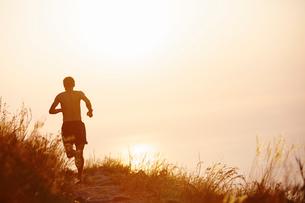 Man running on trail overlooking sunset oceanの写真素材 [FYI02171081]