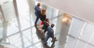 Corporate business people walking in a row in modern office lobbyの写真素材 [FYI02171088]