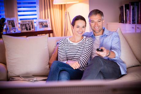Smiling couple watching TV in living roomの写真素材 [FYI02171091]