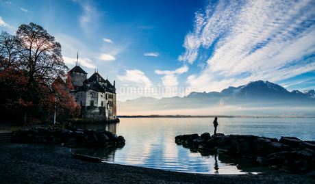 Man on rocks at lakeside outside Chillon Castle, Switzerlandの写真素材 [FYI02171097]