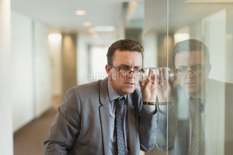 Focused businessman eavesdropping with glass in office corridorの写真素材 [FYI02171115]