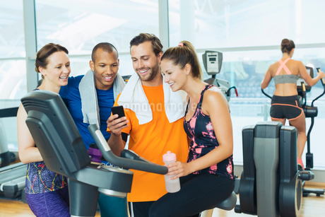 Smiling friends using cell phone at exercise bike in gymの写真素材 [FYI02171140]