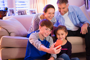 Family taking selfie with camera phone in living roomの写真素材 [FYI02171151]