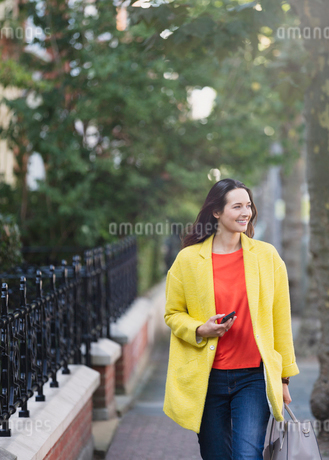 Smiling woman walking with cell phone in urban parkの写真素材 [FYI02171155]