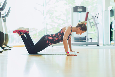 Woman doing push-ups on knees at gymの写真素材 [FYI02171187]
