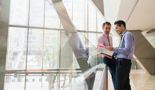 Corporate businessmen discussing paperwork in modern lobbyの写真素材 [FYI02171191]