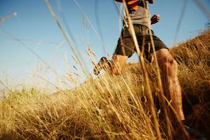 Man running through tall grass on sunny trailの写真素材 [FYI02171207]