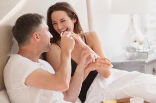 Laughing couple enjoying breakfast in bedの写真素材 [FYI02171237]