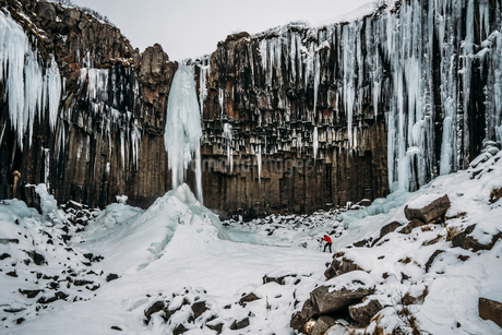 Icicle formations hanging over craggy cliff, Icelandの写真素材 [FYI02171247]