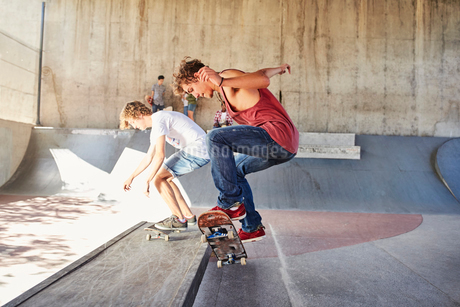 Teenage boys skateboarding at skate parkの写真素材 [FYI02171274]