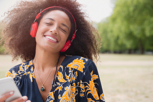 Enthusiastic woman listening to music with headphones and mp3 player in parkの写真素材 [FYI02171277]