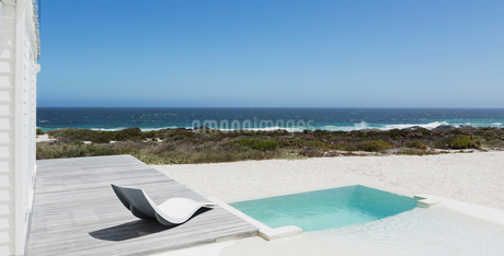 Soaking pool and modern lounge chair with ocean view under sunny blue skyの写真素材 [FYI02171288]