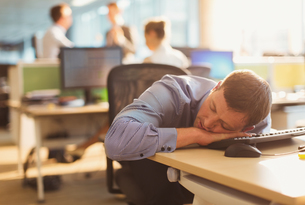Businessman sleeping on desk in officeの写真素材 [FYI02171291]