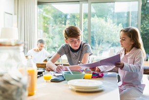 Brother and sister eating breakfast and doing homeworkの写真素材 [FYI02171334]