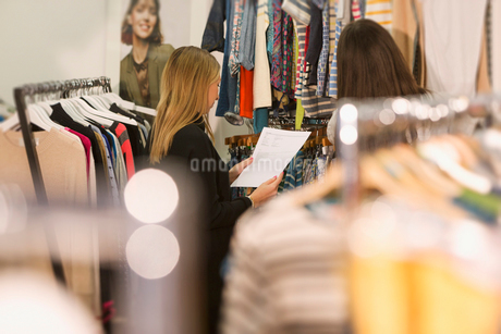 Fashion buyers examining clothing on racksの写真素材 [FYI02171342]
