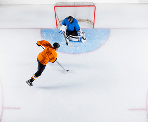 Hockey player shooting the puck at goal netの写真素材 [FYI02171365]