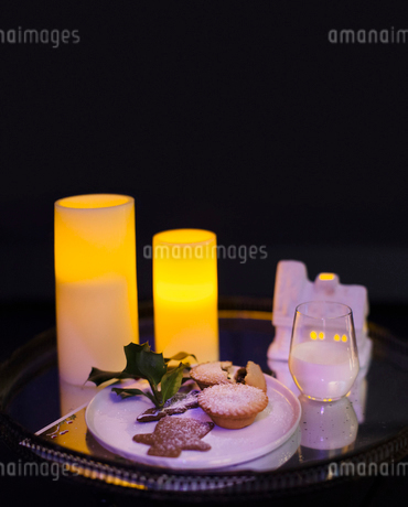 Candles illuminating Christmas cookies and milk left for Santaの写真素材 [FYI02171397]
