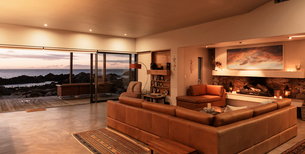 Home showcase interior living room overlooking ocean at sunsetの写真素材 [FYI02171434]