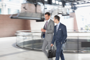 Corporate businessmen with coffee walking and talkingの写真素材 [FYI02171443]