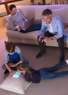 Family relaxing with technology in living room at nightの写真素材 [FYI02171465]