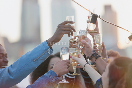 Young adult friends toasting champagne flutes at partyの写真素材 [FYI02171475]