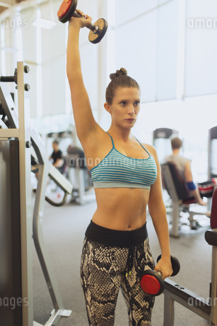 Focused woman lifting dumbbell overhead at gymの写真素材 [FYI02171490]