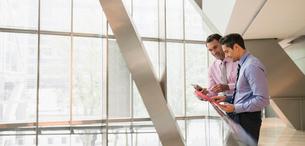 Corporate businessmen using digital tablet at railing in officeの写真素材 [FYI02171499]