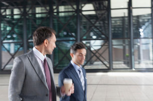 Corporate businessmen with coffee walking and talking outside buildingの写真素材 [FYI02171504]