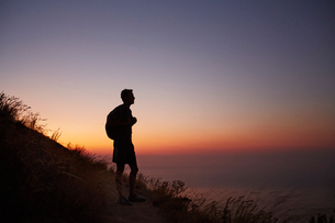 Silhouette of male hiker on trail overlooking ocean at sunsetの写真素材 [FYI02171517]