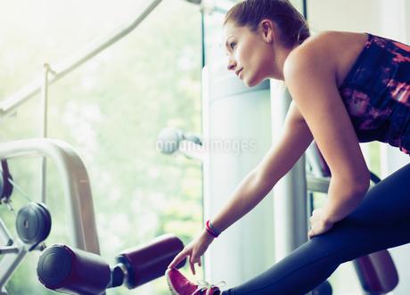 Focused woman stretching leg at gymの写真素材 [FYI02171522]