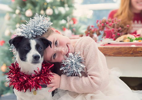 Portrait smiling girl hugging dog with Christmas decorationの写真素材 [FYI02171527]