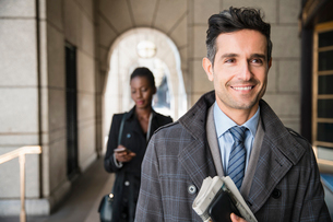 Smiling corporate businessman carrying newspaper and cell phone in cloisterの写真素材 [FYI02171534]
