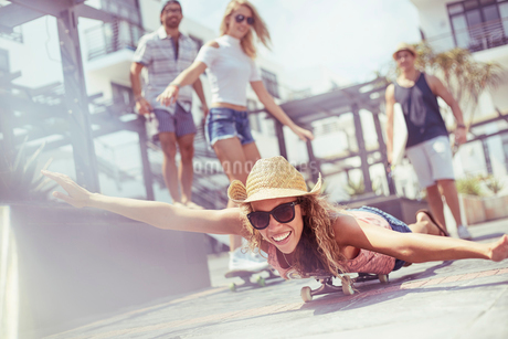 Portrait playful young woman laying riding skateboard on sunny boardwalkの写真素材 [FYI02171550]