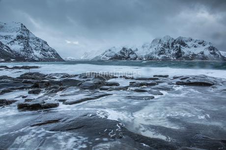 Snow covered mountains behind cold ocean, Vareid, Lofoten Islands, Norwayの写真素材 [FYI02171551]