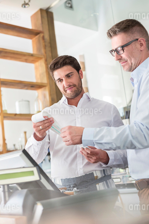 Cafe owner and waiter reviewing receipt at cash registerの写真素材 [FYI02171557]