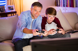 Father and son playing video game in living roomの写真素材 [FYI02171568]