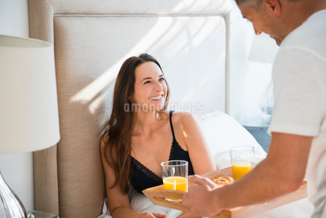 Wife smiling at husband serving breakfast in bedの写真素材 [FYI02171573]