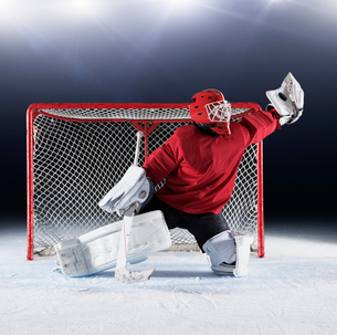 Hockey goalie in red uniform reaching for puck with glove at goal netの写真素材 [FYI02171577]