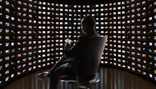 Man watching video on monitorsの写真素材 [FYI02171590]