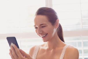Smiling woman texting with cell phone at windowの写真素材 [FYI02171595]