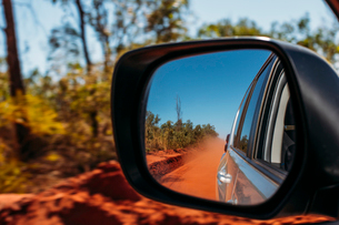 Red clay dust cloud in side-view mirror of carの写真素材 [FYI02171596]