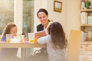 Working mother and daughters at breakfast tableの写真素材 [FYI02171610]