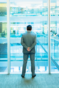 Businessman standing at atrium window with hands behind backの写真素材 [FYI02171634]