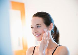 Smiling woman applying face cream to cheekの写真素材 [FYI02171635]