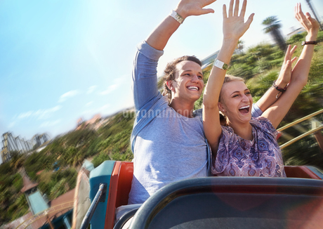 Exhilarated young couple riding amusement park rideの写真素材 [FYI02171642]