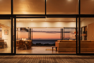 Illuminated home showcase interior overlooking ocean at sunsetの写真素材 [FYI02171643]