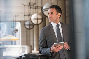 Corporate businessman with digital tablet looking awayの写真素材 [FYI02171660]